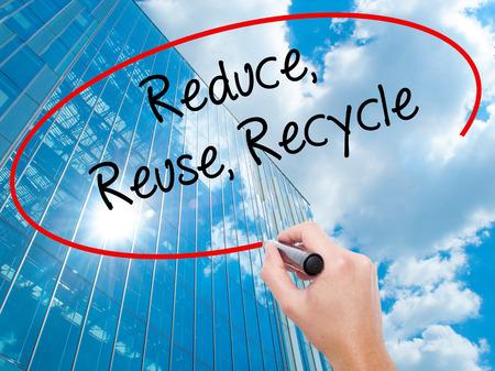 recycle reduce reuse: Escritura de la mano del hombre reduce la reutilización recicla con marcador negro en la pantalla visual. Negocios, la tecnología, el concepto de internet. Fondo moderno de los rascacielos de negocios. Foto de stock