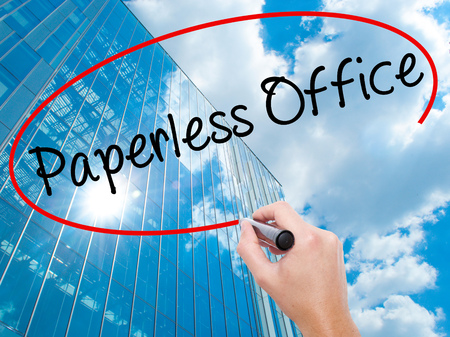 paperless: Man Hand writing Paperless Office  with black marker on visual screen. Business, technology, internet concept. Modern business skyscrapers background. Stock Photo Stock Photo