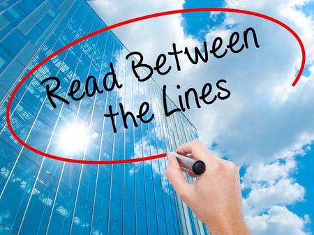 explicitly: Man Hand writing Read Between the Lines   with black marker on visual screen. Business, technology, internet concept. Modern business skyscrapers background. Stock Photo Stock Photo