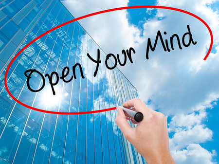 Man Hand writing Open Your Mind with black marker on visual screen.  Business, technology, internet concept. Modern business skyscrapers background. Stock Photo