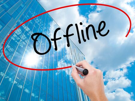 Man Hand writing Offline  with black marker on visual screen. Business, technology, internet concept. Modern business skyscrapers background. Stock Photo