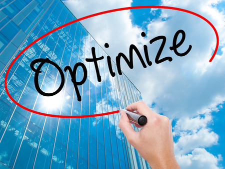 Man Hand writing Optimize with black marker on visual screen.  Business, technology, internet concept. Modern business skyscrapers background. Stock Photo