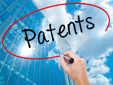 Man Hand writing Patents with black marker on visual screen.  Business, technology, internet concept. Modern business skyscrapers background. Stock Photo