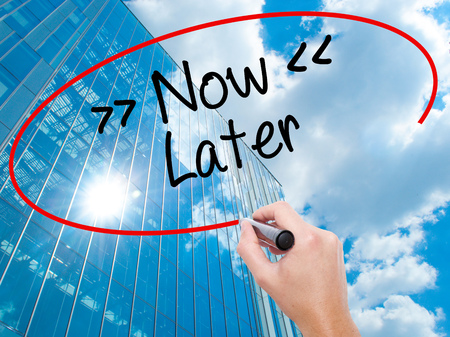 Man Hand writing NowLater with black marker on visual screen.  Business, technology, internet concept. Modern business skyscrapers background. Stock Photo