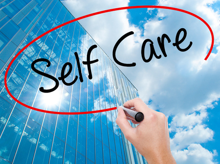 self care: Man Hand writing Self Care with black marker on visual screen.  Business, technology, internet concept. Modern business skyscrapers background. Stock Photo Stock Photo
