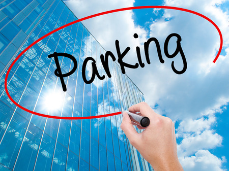 visual screen: Man Hand writing Parking with black marker on visual screen. Business, technology, internet concept. Modern business skyscrapers background. Stock Photo Stock Photo