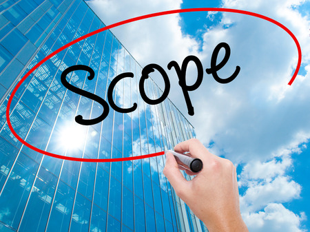 Man Hand writing Scope with black marker on visual screen. Business, technology, internet concept. Modern business skyscrapers background. Stock Photo