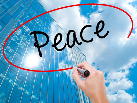 Man Hand writing Peace  with black marker on visual screen.  Business, technology, internet concept. Modern business skyscrapers background. Stock Photo