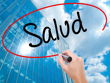 Man Hand writing Salud (Health in Spanish) with black marker on visual screen.  Business, technology, internet concept. Modern business skyscrapers background. Stock Photo Stock Photo