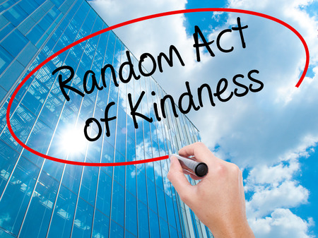 Man Hand writing Random Act of Kindness with black marker on visual screen. Business, technology, internet concept. Modern business skyscrapers background. Stock Photo