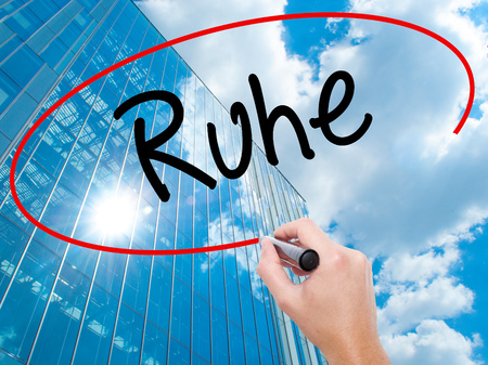 Man Hand writing Ruhe (Quiet in German) with black marker on visual screen.  Business, technology, internet concept. Modern business skyscrapers background. Stock Photo