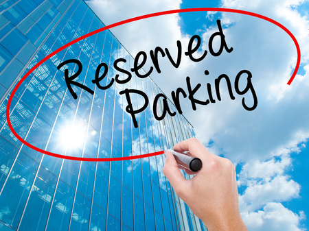 Man Hand writing Reserved Parking with black marker on visual screen. Business, technology, internet concept. Modern business skyscrapers background. Stock Photo