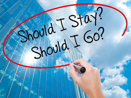 indecisiveness: Man Hand writing Should I Stay? Should I Go? with black marker on visual screen. Business, technology, internet concept. Modern business skyscrapers background. Stock Photo Stock Photo