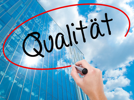 Man Hand writing Quality (Qualitat in German) with black marker on visual screen.  Business, technology, internet concept. Modern business skyscrapers background. Stock Photo