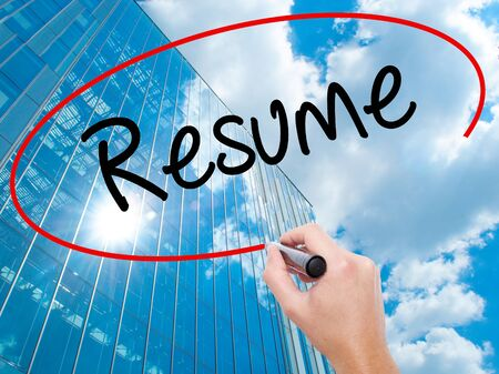 Man Hand writing Resume with black marker on visual screen.  Business, technology, internet concept. Modern business skyscrapers background. Stock Photo