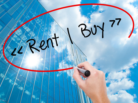 Man Hand writing Rent - Buy  with black marker on visual screen.  Business, technology, internet concept. Modern business skyscrapers background. Stock Photo Stock Photo