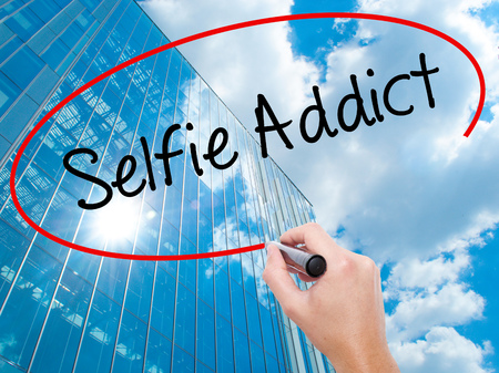 Man Hand writing Selfie Addict with black marker on visual screen.  Business, technology, internet concept. Modern business skyscrapers background. Stock Photo Stock Photo