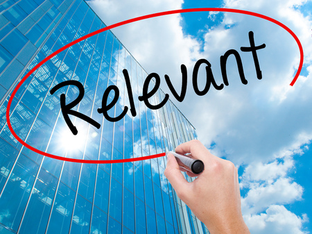 relevant: Man Hand writing Relevant with black marker on visual screen.  Business, technology, internet concept. Modern business skyscrapers background. Stock Photo