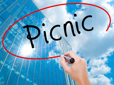 picknick: Man Hand writing Picnic with black marker on visual screen. Business, technology, internet concept. Modern business skyscrapers background. Stock Photo