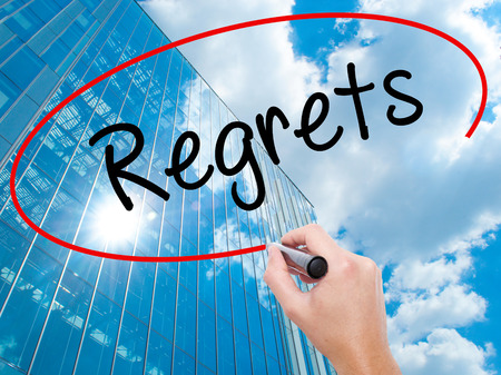 remorse: Man Hand writing  Regrets with black marker on visual screen. Business, technology, internet concept. Modern business skyscrapers background. Stock Photo