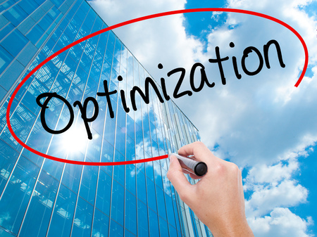 Man Hand writing Optimization  with black marker on visual screen.  Business, technology, internet concept. Modern business skyscrapers background. Stock Photo Stock Photo