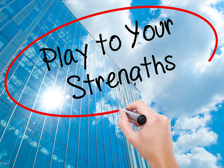 Man Hand writing Play to Your Strengths with black marker on visual screen.  Business, technology, internet concept. Modern business skyscrapers background. Stock Photo
