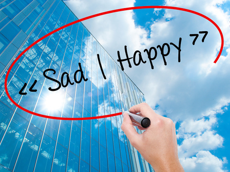 Man Hand writing Sad - Happy with black marker on visual screen.  Business, technology, internet concept. Modern business skyscrapers background. Stock Photo Stock Photo