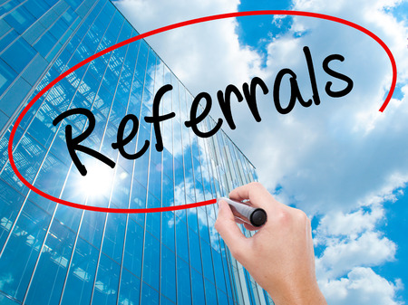 Man Hand writing Referrals with black marker on visual screen.  Business, technology, internet concept. Modern business skyscrapers background. Stock Photo