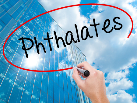 Man Hand writing  Phthalates  with black marker on visual screen.  Business, technology, internet concept. Modern business skyscrapers background. Stock Photo