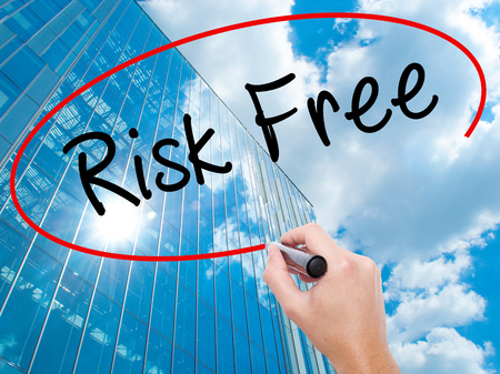Man Hand writing Risk Free with black marker on visual screen. Business, technology, internet concept. Modern business skyscrapers background. Stock Image