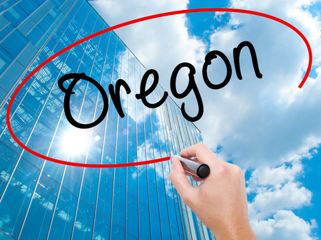 west river: Man Hand writing Oregon with black marker on visual screen. Business, technology, internet concept. Modern business skyscrapers background. Stock Photo