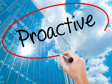 Man Hand writing Proactive with black marker on visual screen.  Business, technology, internet concept. Modern business skyscrapers background. Stock Photo