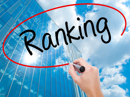 Man Hand writing Ranking with black marker on visual screen. Business, technology, internet concept. Modern business skyscrapers background. Stock Photo