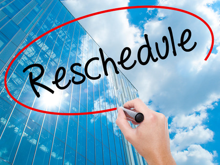 Man Hand writing Reschedule  with black marker on visual screen.  Business, technology, internet concept. Modern business skyscrapers background. Stock Photo