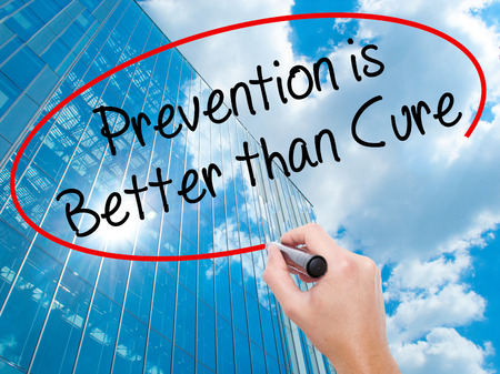 cure prevention: Man Hand writing Prevention is Better than Cure with black marker on visual screen. Business, technology, internet concept. Modern business skyscrapers background. Stock Photo Stock Photo