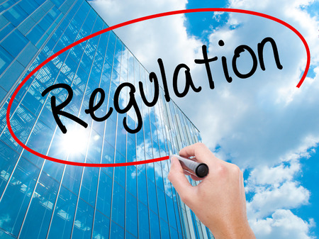 Man Hand writing Regulation  with black marker on visual screen. Business, technology, internet concept. Modern business skyscrapers background. Stock Photo Stock Photo