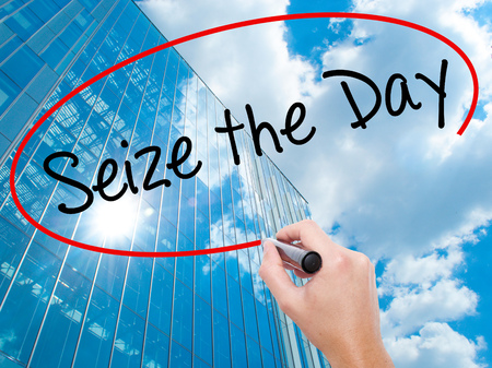 Man Hand writing Seize the Day with black marker on visual screen.  Business, technology, internet concept. Modern business skyscrapers background. Stock Photo Stock Photo