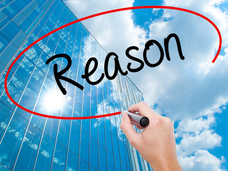 Man Hand writing Reason with black marker on visual screen.  Business, technology, internet concept. Modern business skyscrapers background. Stock Photo