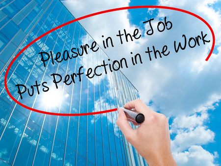 perfectionist: Man Hand writing Pleasure in the Job Puts Perfection in the Work with black marker on visual screen.  Business, technology, internet concept. Modern business skyscrapers background. Stock Photo