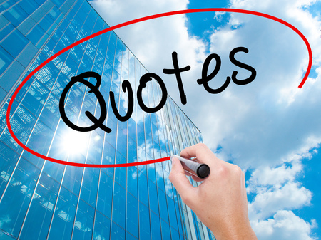 Man Hand writing Quotes  with black marker on visual screen.  Business, technology, internet concept. Modern business skyscrapers background. Stock Photo