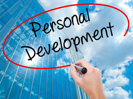 Man Hand writing Personal Development  with black marker on visual screen.  Business, technology, internet concept. Modern business skyscrapers background. Stock Photo Stock Photo