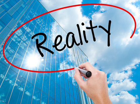 business skeptical: Man Hand writing  Reality with black marker on visual screen. Business, technology, internet concept. Modern business skyscrapers background. Stock Photo