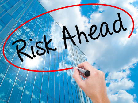 Man Hand writing Risk Ahead with black marker on visual screen. Business, technology, internet concept. Modern business skyscrapers background. Stock Image