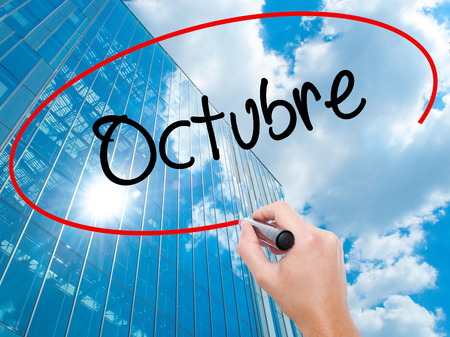 """Man Hand writing """"Octubre"""" (In Spanish: October) with black marker on visual screen. Business, technology, internet concept. Stock Photo"""