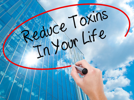 toxins: Man Hand writing Reduce Toxins In Your Life with black marker on visual screen. Business, technology, internet concept. Modern business skyscrapers background. Stock Photo Stock Photo