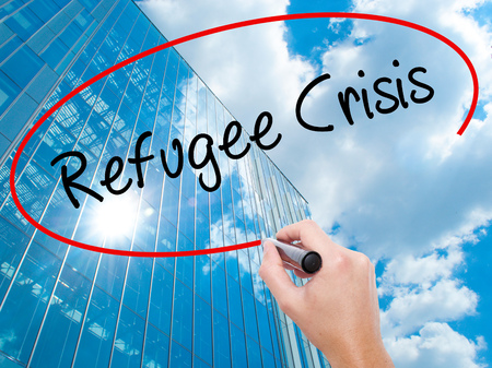 Man Hand writing Refugee Crisis with black marker on visual screen.  Business, technology, internet concept. Modern business skyscrapers background. Stock Photo