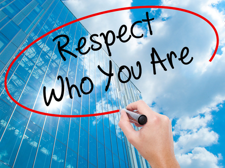 Man Hand writing Respect Who You Are with black marker on visual screen.  Business, technology, internet concept. Modern business skyscrapers background. Stock Photo