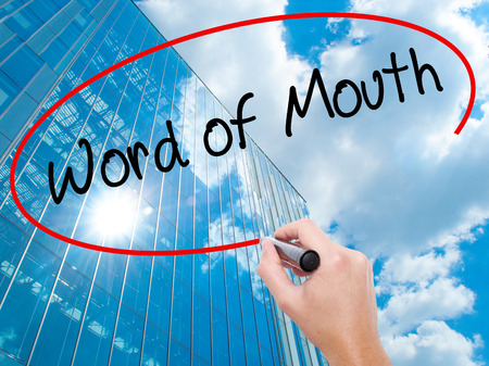 Man Hand writing Word of Mouth  with black marker on visual screen.  Business, technology, internet concept. Modern business skyscrapers background. Stock Photo Stock Photo