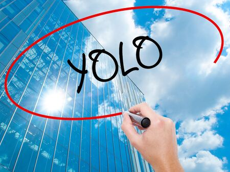 Man Hand writing YOLO (You Only Live Once) with black marker on visual screen. Business, technology, internet concept. Modern business skyscrapers background. Stock Photo