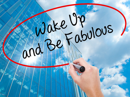 Man Hand writing Wake Up and Be Fabulous with black marker on visual screen.  Business, technology, internet concept. Modern business skyscrapers background. Stock Photo